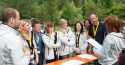 Sommerfest zum 50. Jubiläum von TFA Dostmann. Mitarbeiter stehen in einer Gruppe und hören einer Aufgabenstellung für ein Spiel zu.