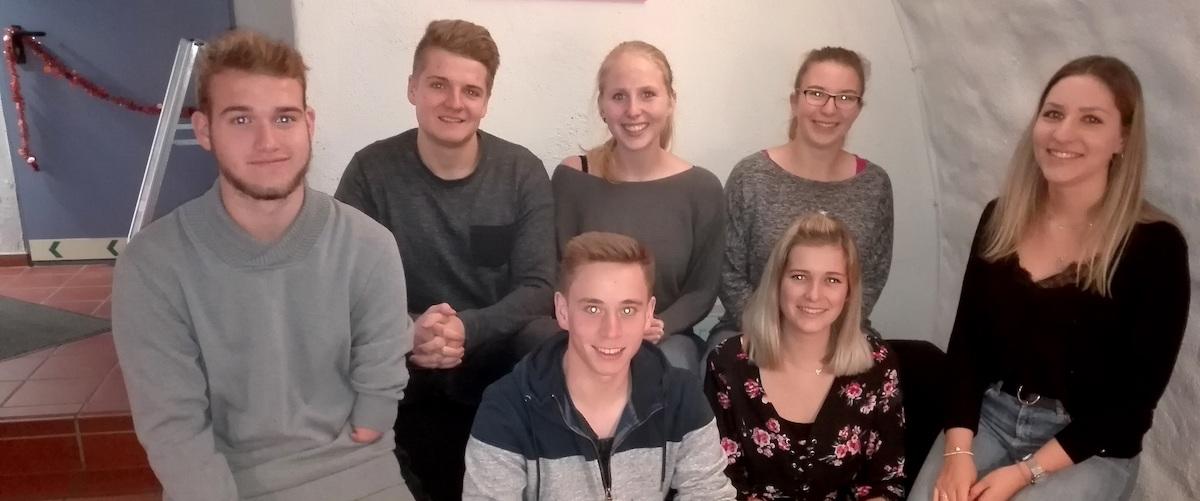 Gruppe junger Menschen, die lächeln. Es sind die TFA Azubis im Foyer des Escape Rooms in Würzburg.