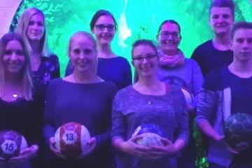 Gruppe junger Menschen mit Bällen in der Hand. Es sind die TFA Azubis bei ihrem Ausflug nach Würzburg zum Pool-Ball spielen.
