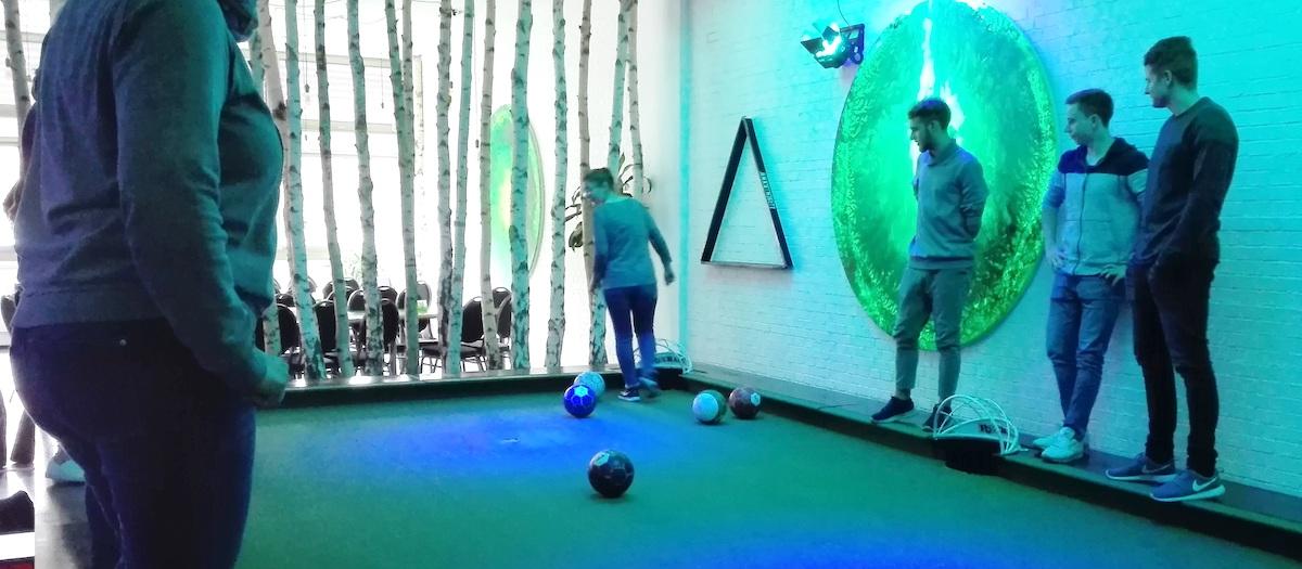 Das Spielfeld vom Pool-Ball ist sichbar mit den teilnehmenden Spielern. Ein Mädchen schießt gerade. Es sind die Azubis von TFA Dostmann bei ihrem Ausflug nach Würzburg zum Pool-Ball spielen.
