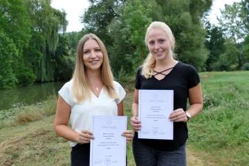 Foto von Marie-Lena Kranz und Hannah Schlör mit der Auszeichnung für herausragende Prüfungsleistungen in der IHK-Abschlussprüfung zur Industriekauffrau bei TFA Dostmann.