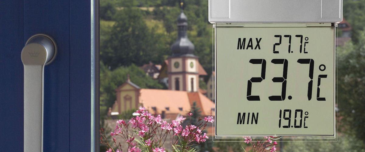 Digitales Fensterthermometer VISION von TFA Dostmann, angebracht an einem Fenster. Ausblick auf ein historisches Gebäude.