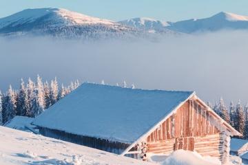 Winterlandschaft in den Bergen mit einer verschneiten Holzhütte und in warmen Sonnenlicht. Es ist das Headerbild für den Wettertrend für Deutschland vom 11. Januar 2019 von TFA Dostmann