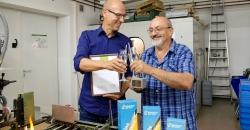 Geschäftsführer Axel Dostmann und Glasbläsermeister Ewald Kunkel sind stolz über den Award für das nachhaltige Produkt: Trinkhalme aus Glas GlasWerk. In einer kleinen Runde stoßen sie auf die Auszeichnung an. Im Hintergrund sieht man die Produktionsstätte der Trinkhalme.