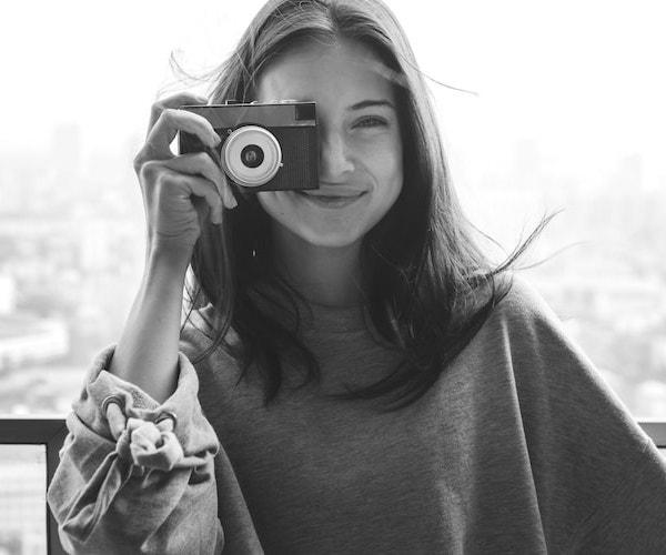 Eine junge Frau mit einer Kamera in der Hand, ist glücklich. Sie ist Influencerin und steht für die Community #TFAfriends