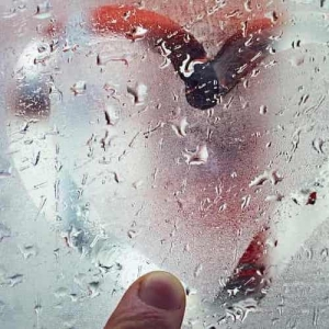A fogged window on which someone draws a heart with his finger. It is the header image for the theme world humidity of TFA Dostmann.