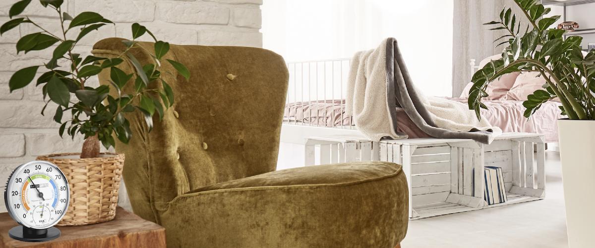 Wohnraum mit einem Sessel und auf dem Beistelltsich steht ein analoges Hygrometer von TFA Dostmann.