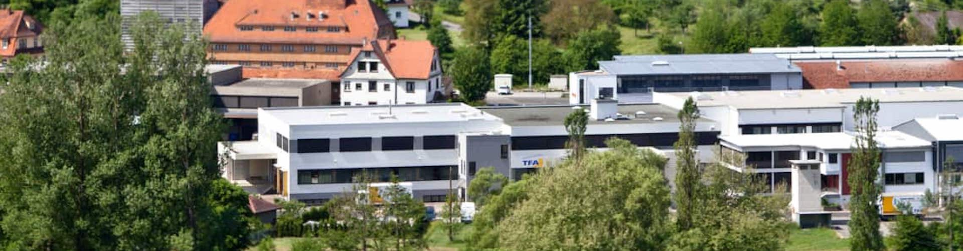 Outdoor view of the TFA Dostmann company building in Reicholzheim in the lovely Tauber valley. The company is located in the middle of the rural area, close to the banks of the Tauber and surrounded by green trees.