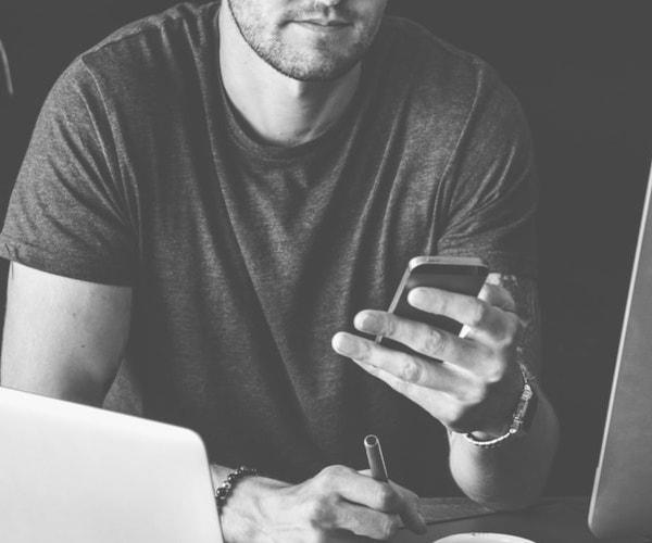 Ein junger Mann vor einem Computer und mit Smartphone in der Hand, erstellt gerade einen Beitrag. Er ist Teil der #TFAfriends Community.