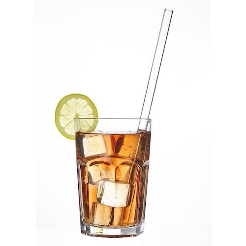 Longdrinkglas gefüllt mit einem Getränk und Eiswürfeln, ein Trinkhalm Strohhalm aus Glas von TFA Dostmann ist im Glas und eine Scheibe Limette ziert den Glasrand.