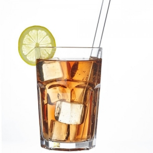 Long drink glass filled with a drink and ice cubes, a drinking straw Straw glass from TFA Dostmann is in the glass and a slice of lime graces the rim of the glass.