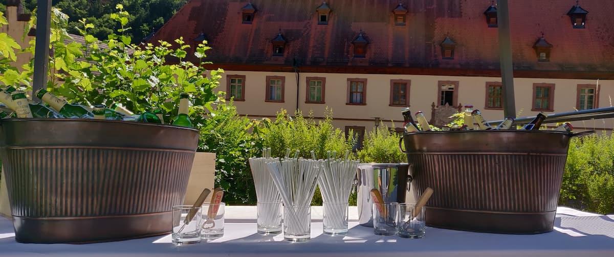 Glastrinkhalme von TFA stehen auf einem Tisch mit Getränken. Sommerliche Stimmung. Das Bild mit dem Glastrinkhalmen GlasWerk zeigt, wie man die Glasstrohhalme aufbewahren kann.