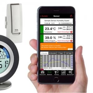 Auf dem Display des Smartphones sind Beispiele für gemessene Daten in der WeatherHub App zu sehen. Im Hintergrund erkennt man exemplarisch ein Gateway sowie einen Sender.