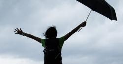 Eine Frau steht mit einem Schirm in der Hand in einer verregneten Landschaft und streckt die Arme in die Luft in Richtung wolkenverhangenem Himmel. Der TFA Wettertrend für Deutschland prognostiziert Unwetter.