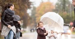 Wettertrend für Deutschland von TFA. Bei Regenwetter geht eine junge Familie trotzdem spazieren mit einem Regenschirm.