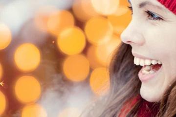 Junge Frau lacht und hält eine Wunderkerze in der Hand. Sie ist warm angezogen mit einer roten Mütze und Handschuhen. Es ist das Headerbild für den Wettertrend vom 28. Dezember 2018 von TFA Dostmann
